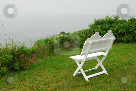 Bench on ocean shore stock photo, White wooden bench on the Atlantic ocean shore in Maine, US, on a foggy day by Elena Elisseeva