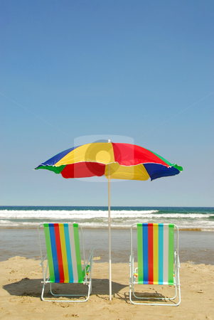 Beach chairs and umbrella stock photo, Beach chairs and umbrella on the ocean shore with surf in the background by Elena Elisseeva