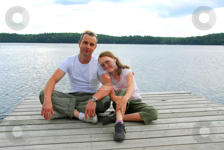 Father child lake stock photo, Father and child sitting on a wooden pier on a lake in nothern Ontrario by Elena Elisseeva
