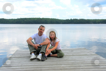 Father child lake stock photo, Father and child sitting on a wooden pier on a lake by Elena Elisseeva