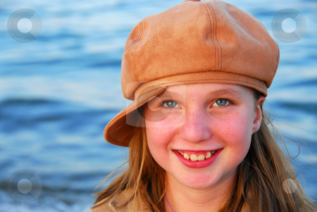 Smiling girl in a hat stock photo, Cute preteen girl smiling wearing suede hat, blue water background by Elena Elisseeva