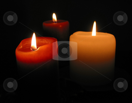 Burning candles stock photo, Three candles burning in the dark, focus on the front candle by Elena Elisseeva