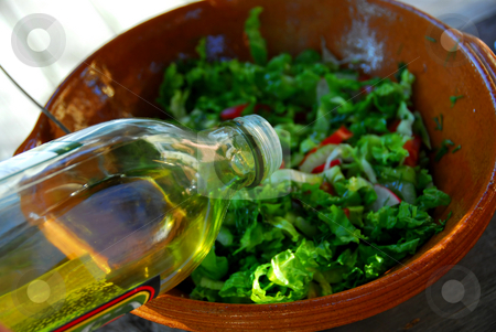 Garden salad and olive oil stock photo, Olive oil being poured into garden salad for salad dressing by Elena Elisseeva