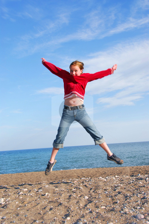Girl child jumping stock photo, Young girl jumping on a beach by Elena Elisseeva