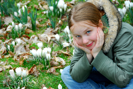 Spring girl stock photo, Beautiful young girl sitting among blooming spring flowers by Elena Elisseeva