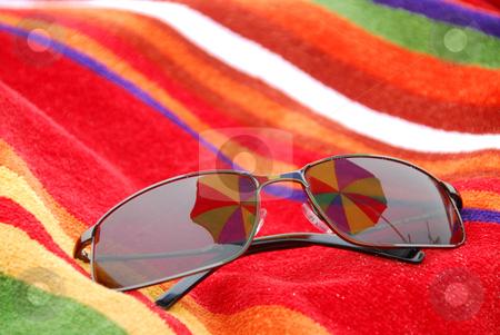 Beach sunglasses stock photo, Sunglasses on beach towel relfecting beach umbrella above them by Elena Elisseeva