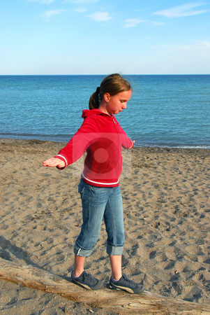 Girl balancing on log stock photo, Young girl balancing on log on a sandy beach by Elena Elisseeva