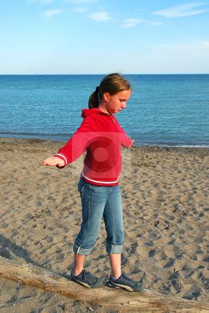 Girl balancing on log stock photo, Young girl balancing on log on a sandy beach by Elena Elisseeva