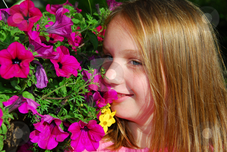 Young girl with flowers stock photo, Portrait of a young girl with pink petunias by Elena Elisseeva