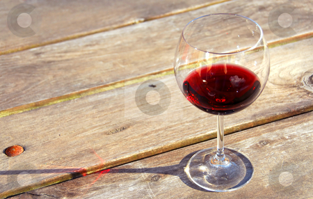 Glass of red wine stock photo, Glass of red wine on old rustic table by Elena Elisseeva