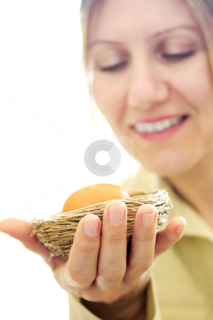 Mature woman holding a nest with an egg stock photo, Mature woman holding a nest with an egg - investment concept by Elena Elisseeva