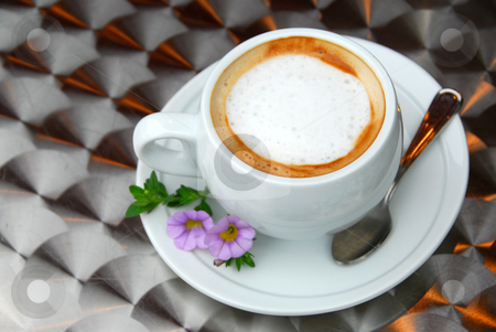 Cup of coffee stock photo, Cup of coffee with flowers on saucer on a table with metallic surface by Elena Elisseeva