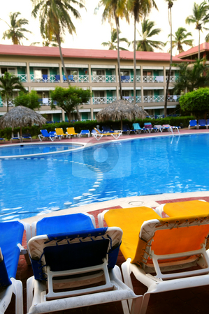 Swimming pool stock photo, Swimming pool and chairs at tropical resort by Elena Elisseeva