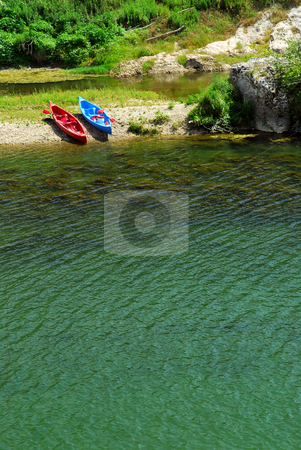 Kayaks on river bank stock photo, Kayaks on the bank of river Gard in southern France near Nimes by Elena Elisseeva