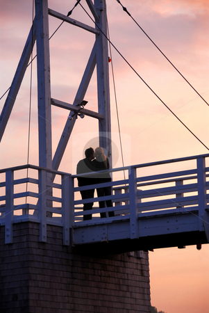 Couple kissing on a bridge stock photo, Couple kissing on pedestrian bridge at sunset  in Perkins Cove, Maine by Elena Elisseeva