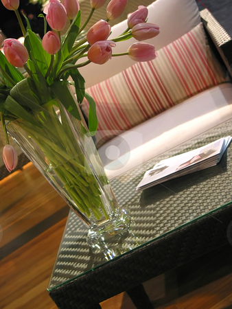 Interior furnuture vase stock photo, Vase of pink tulips on a coffee table in from of a chair in a living room by Elena Elisseeva