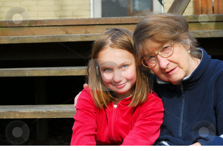 Two generations stock photo, Grandmother and granddaughter sitting on a deck by Elena Elisseeva
