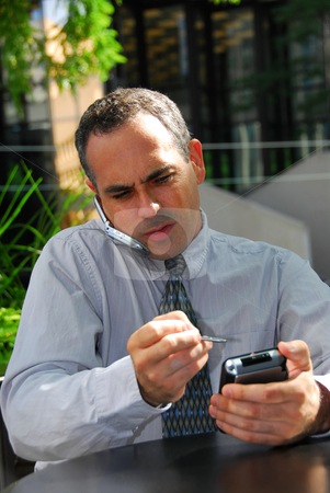 Businessman busy stock photo, Busy businessman talking on cell phone and working on his palm pilot by Elena Elisseeva