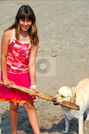 Girl play dog stock photo, Young pretty girl playing with a dog on a beach by Elena Elisseeva