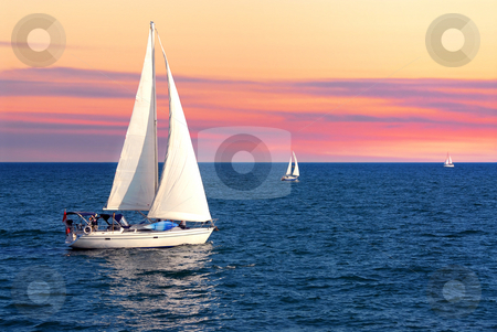Sailboats at sunset stock photo, Sailboat sailing towards sunset on a calm evening by Elena Elisseeva