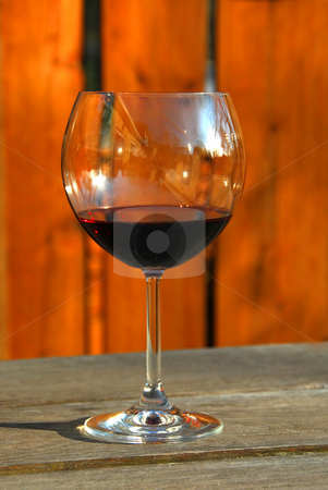 Glass of red wine stock photo, Glass of red wine on old rustic table, vertical by Elena Elisseeva