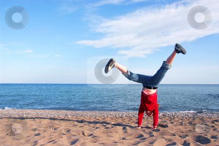 Girl doing cartwheel stock photo, Young girl doing cartwheel on a beach by Elena Elisseeva