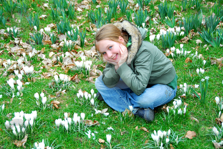 Girl in crocus field stock photo, Young girl sitting among blooming white crocuses by Elena Elisseeva
