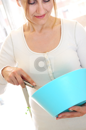 Mature woman cooking at home stock photo, Casual mature woman enjoying cooking at home by Elena Elisseeva