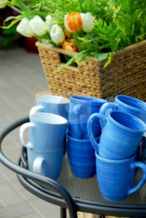 Cups stock photo, Blue cups and flower basket on a metal side table by Elena Elisseeva