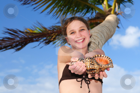 Young girl with seashell stock photo, Happy young girl holding a large seashell on tropical beach by Elena Elisseeva