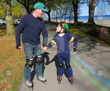 Father son rollerblade stock photo, Father and son rollerblading by Elena Elisseeva