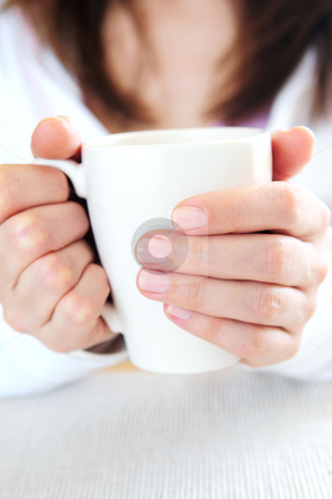 Hands holding a cup stock photo, Hands of a mature woman holding a cup by Elena Elisseeva