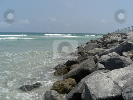 The ocean bolders stock photo, Huge rocks and bolders are lined at the edge of the ocean in Ponce Inlet, FL. by Rebecca Mosoetsa