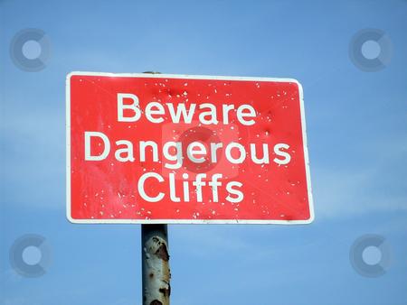 Beware Dangerous Cliffs sign stock photo, Beware Dangerous Cliffs sign, blue sky background. by Martin Crowdy