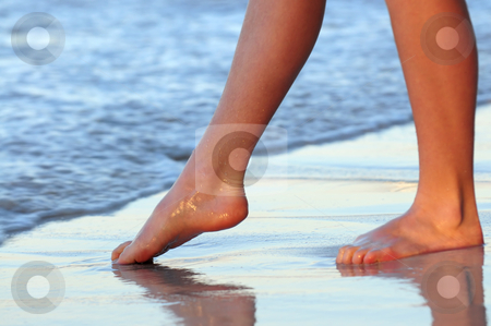 Trying water stock photo, Feet of a young woman trying water on tropical beach by Elena Elisseeva