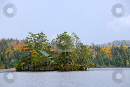 Cabin on island stock photo, Wooden cozy cabin on a small island on a scenic lake by Elena Elisseeva