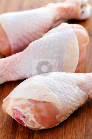 Raw chicken drumsticks stock photo, Raw chicken drumsticks on a wooden cutting board by Elena Elisseeva