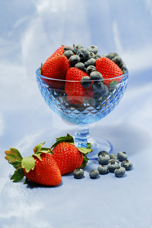 Berry still life stock photo, Strawberries and blueberries in blue glass bowl on blue background by Elena Elisseeva