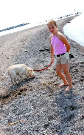 Girl walking dog stock photo, Young girl walking a dog on a beach by Elena Elisseeva