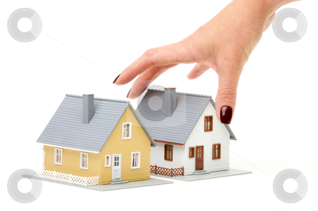 Choosing A Home stock photo, Female hand reaching for house isolated on a white background. by Andy Dean