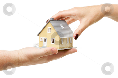 Reaching For A Home stock photo, Female hand reaching for a house isolated on a white background. by Andy Dean