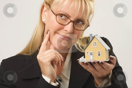 Thinking of a Home stock photo, Female holding small house. by Andy Dean