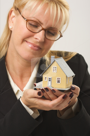 Woman Holding House stock photo, Female holding and looking at small house. by Andy Dean