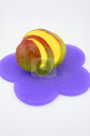 Mango stock photo, A mango, sliced and fanned out, on a purple cutting board. by Jessica Tooley