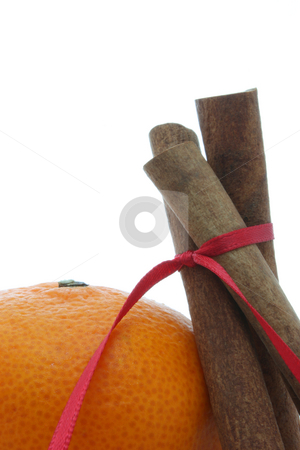 Cinnamon stock photo, Three cinnamon sticks tied with a red ribbon, leaning against a mandarin orange, isolated on white. by Jessica Tooley