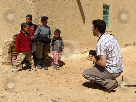 Rich and Poor stock photo, A white photographer taking a picture of Arab children in rural Morocco. by Jessica Tooley