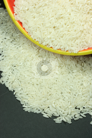 Bowl of Rice stock photo, A bowl of rice spilling out on a black background. by Jessica Tooley