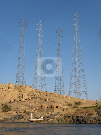 Progress stock photo, Electricity transmission lines loom over traditional homes on the Nile in Egypt. by Jessica Tooley
