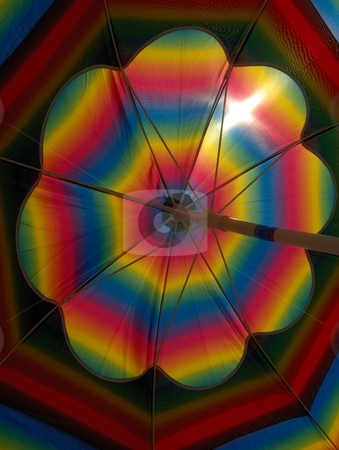 Parasol stock photo, A close-up of a bright, rainbow colored beach umbrella by Jessica Tooley