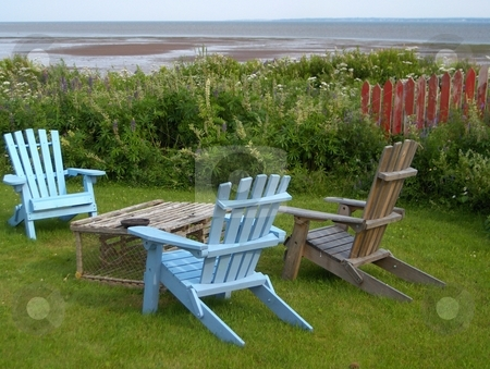 Ocean View stock photo, Three adriondack chairs with a lobster trap for a coffee table in a yard overlooking the ocean. by Jessica Tooley